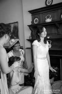 Hazels Mum and bridesmaids helping her with the dress