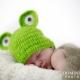 Newborn wearing a frog hat