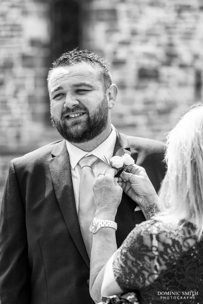 Groom having his buttonhole done